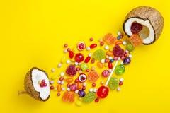 糖果五颜六色的爆炸在椰子的在黄色上色了背景,创造性的静物画,平的位置样式 免版税图库摄影