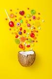 糖果五颜六色的爆炸在椰子的在黄色上色了背景,创造性的静物画,平的位置样式 免版税库存照片