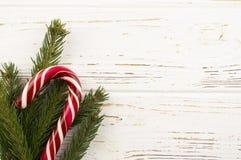 糖果和云杉的分支在白色木背景 背景新年度 免版税库存照片