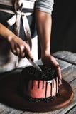 糖果商切开蛋糕用巧克力和装饰用无核小葡萄干和桑树 乡村模式 免版税库存照片