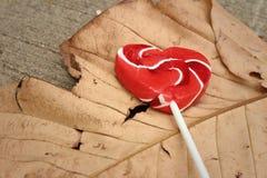 糖果在一片棕色叶子的华伦泰心脏 免版税库存图片