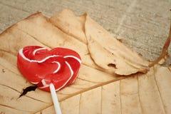 糖果在一片棕色叶子的华伦泰心脏 库存照片