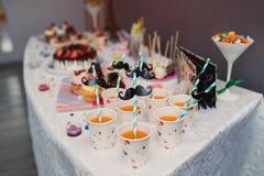 糖果瓶子和饮料在一张点心桌上在党或婚礼庆祝 库存照片