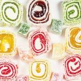 糖果背景 色的糖果包裹在卷和洒与椰子剥落 土耳其快乐糖 免版税库存图片
