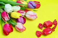 糖果郁金香篮子和花束在黄色背景的 礼物一个假日 库存照片