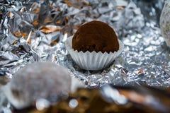 糖果,鲜美从自然巧克力,以球的形式 从箔的安心背景 光光戏剧和补丁  免版税库存照片