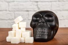 糖概念害处  糖和黑头骨形象立方体  免版税库存图片