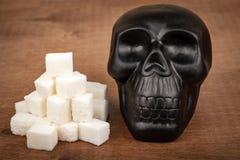 糖概念害处  糖和黑头骨形象立方体  免版税库存照片