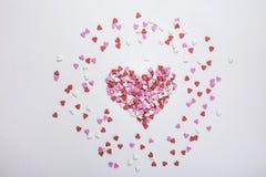 糖洒在白色背景驱散的心脏形状的糖果 华伦泰拉丁文的生日慈善标志 库存照片
