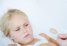 给糖浆女孩的匙子医生 免版税库存图片