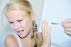 给糖浆女孩的匙子医生 库存图片