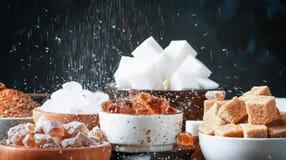 糖的被分类的不同的类型在碗的在黑暗的一张桌上 免版税库存照片