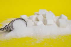 糖立方体和糖背景在匙子 在黄色背景的白糖 免版税图库摄影