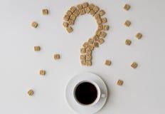 糖立方体塑造了作为一杯问号和咖啡在白色背景的 饮食unhealty甜瘾概念 免版税库存照片