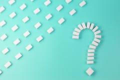 糖立方体塑造了作为在绿松石背景的一个问号标志 免版税库存照片