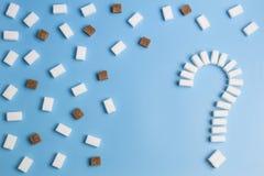 糖立方体塑造了作为在蓝色背景的一个问号标志 免版税图库摄影