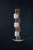 糖立方体金字塔在茶匙的 免版税库存照片