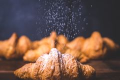 糖粉末倾吐在一个新近地被烘烤的新月形面包上 免版税图库摄影