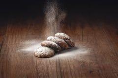 糖粉末在一张木桌上的自创曲奇饼被撒布 免版税图库摄影