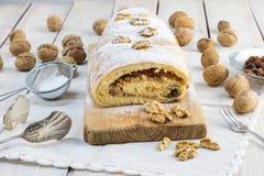 糖衣核桃果馅奶酪卷用核桃和葡萄干在木b 免版税图库摄影