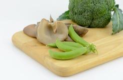 糖豌豆,犹太人的耳朵在切板的蘑菇硬花甘蓝 库存照片
