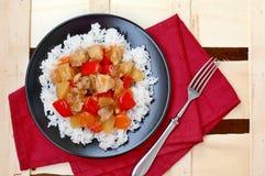 糖醋食物用在红色布料的米、红辣椒、菠萝、葱和鸡肉在木背景的黑色的盘子 免版税库存图片