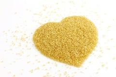 糖,心形从甘蔗顶视图的糖,黄褐色背景的砂糖,蔗糖红色糖堆 免版税库存图片
