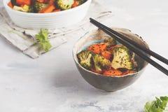 糙米用被烘烤的硬花甘蓝和白薯在白色backgro 免版税库存照片