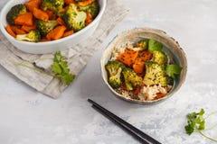 糙米用被烘烤的硬花甘蓝和白薯在白色backgro 免版税库存图片
