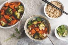 糙米用被烘烤的硬花甘蓝和白薯在白色backgro 库存照片