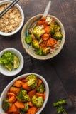 糙米用被烘烤的硬花甘蓝和白薯,黑暗的背景 免版税库存图片