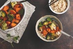 糙米用被烘烤的硬花甘蓝和白薯,黑暗的背景 库存图片