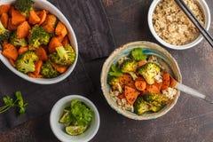 糙米用被烘烤的硬花甘蓝和白薯,黑暗的背景 库存照片