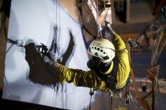 系住通入工作在高度的建筑工人画家 免版税库存图片