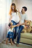 系列三 怀孕的妈妈、爸爸和小女儿 库存照片