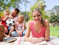 系列她的野餐读取微笑的妇女 库存图片