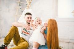 系列愉快三 妈妈,爸爸,孩子礼服戏剧的,笑,微笑一个岁女孩在明亮的屋子里 晴朗的天气 免版税图库摄影