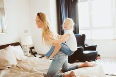 系列愉快家庭使用 母亲和小孩女儿放松和获得乐趣在床上 免版税库存照片