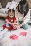 系列愉快爱 在儿童居室照顾和茶党她的女儿女孩的戏剧并且喝从杯子的茶 滑稽的妈妈和 免版税库存图片