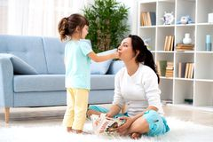 系列愉快爱 美丽的母亲和一点女儿获得乐趣,戏剧在地板上的屋子里,拥抱,微笑并且无所事事  免版税库存图片