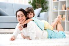 系列愉快爱 美丽的母亲和一点女儿获得乐趣,戏剧在地板上的屋子里,拥抱,微笑并且无所事事  免版税库存照片