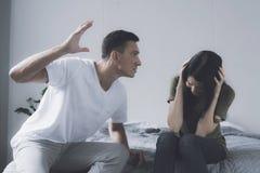 系列问题 一个人摇摆击中在他旁边坐床并且盖自己用她的手的妇女 库存照片
