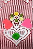 系带与心脏的小垫布在与形成Valenine设计的保险开关心脏和工艺花的红色背景 免版税库存照片