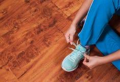 系带绿色运动鞋的一个少妇的手 以与拷贝空间的一个木地板为背景 免版税库存图片