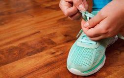 系带绿色运动鞋的一个少妇的手 以与拷贝空间的一个木地板为背景 库存照片
