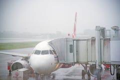 素叻他尼,泰国- 11月11 :在大雨、连接aircr的亚洲航空登陆的在素叻国际机场,安全和桥梁 库存照片