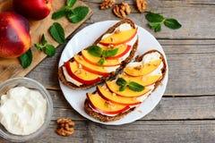 素食三明治用乳脂干酪、油桃、核桃和薄菏在服务板材和在老木背景 图库摄影
