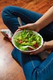 素食主义者在碗的早餐膳食用各种各样的新鲜的混合沙拉离开和蕃茄 拿着与膝盖和手visib的牛仔裤的女孩叉子 免版税图库摄影