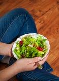 素食主义者在碗的早餐膳食用各种各样的新鲜的混合沙拉离开和蕃茄 拿着与膝盖和手visib的牛仔裤的女孩叉子 免版税库存照片