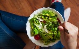 素食主义者在碗的早餐膳食用各种各样的新鲜的混合沙拉离开和蕃茄 拿着与膝盖和手visib的牛仔裤的女孩叉子 图库摄影